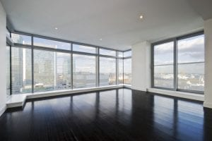 empty apartment with hard wood floor an floor to ceiling windows